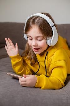 Bambina in abiti gialli si trova sul letto e comunica sui social network tramite smartphone