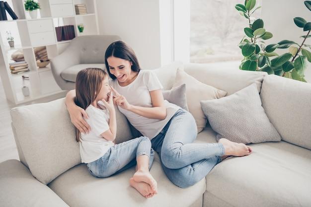 Bambina giovane mamma che abbraccia giocando touch naso ridendo in casa casa al chiuso