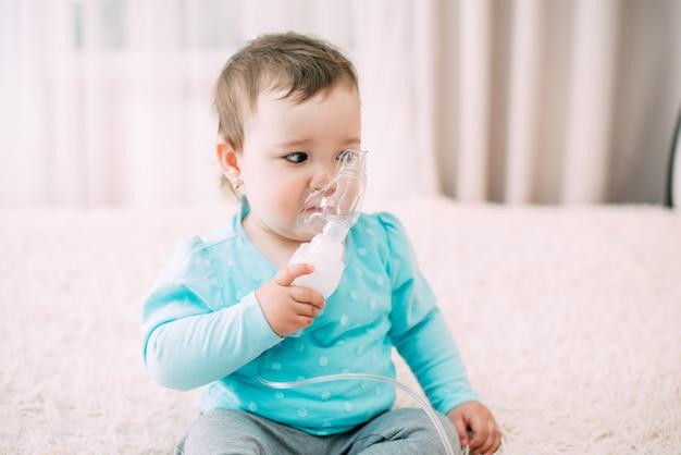 Una bambina tu stessa che regge la maschera del nebulizzatore, rendendo l'inalazione molto dolce