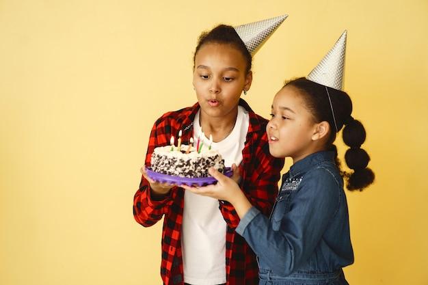 Compleanno di bambine isolato sulla parete gialla. bambini che tengono la torta.