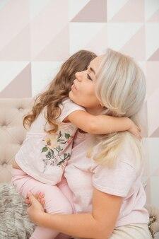 Bambine dall'aspetto caucasico abbraccia teneramente sua madre in un luminoso soggiorno in stile scandinavo