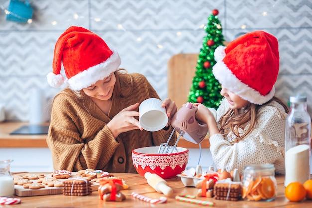 Bambine che cucinano pan di zenzero di natale. cuocere e cucinare con i bambini per il natale a casa.