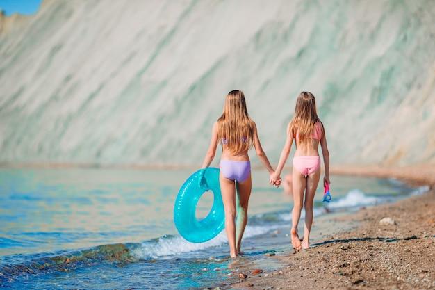 Bambine divertendosi alla spiaggia tropicale che giocano insieme