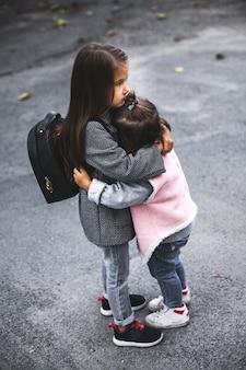 Le bambine si abbracciano in strada. elegantemente vestito. uomo, moda, relazione, amore