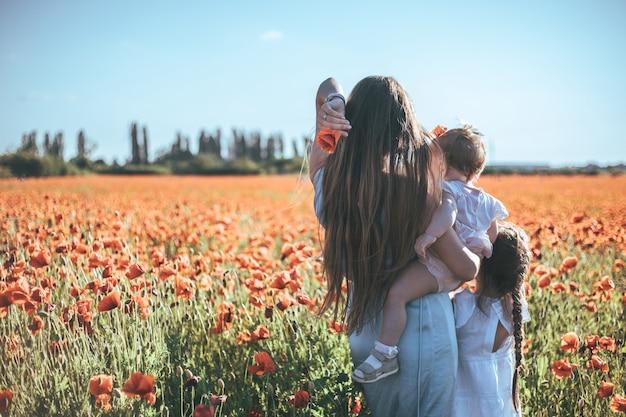 Bambine e madre in abiti bianchi e ghirlande che camminano di papaveri sul campo di papaveri