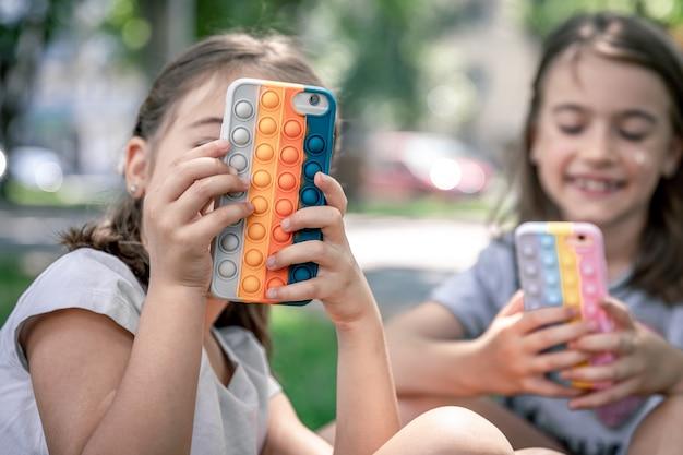 Le bambine all'aperto con i telefoni in una custodia con brufoli pop it, un giocattolo antistress alla moda.
