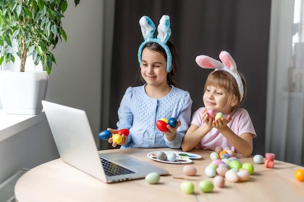 Bambine che dipingono le uova di pasqua con un computer portatile.