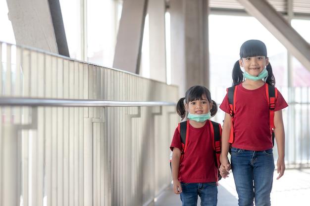 Bambine e sorelle in maschere protettive con zaini scolastici. vista degli studenti delle scuole elementari che trasportano una borsa da scuola.