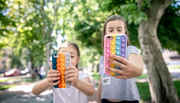 Le bambine usano i telefoni in custodie alla moda per antistress.