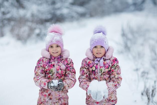 Le bambine a winter park giocano con la neve nel parco