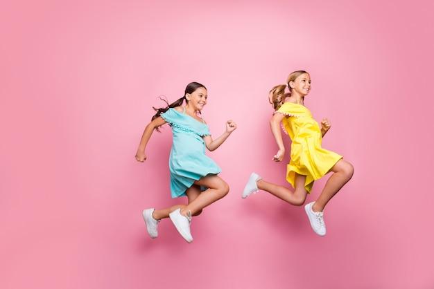 Bambine con le trecce in posa contro il muro rosa