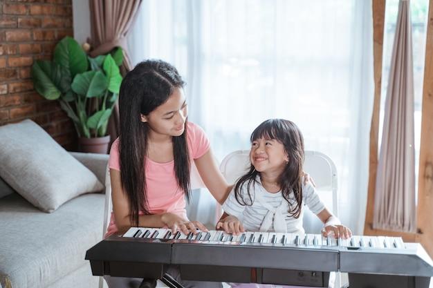 Le bambine con il sorriso suonano la tastiera di uno strumento musicale
