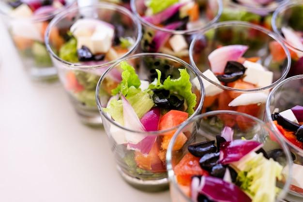 Bicchieri con insalate fresche, uova, salmone e cetrioli in piedi sul tavolo bianco