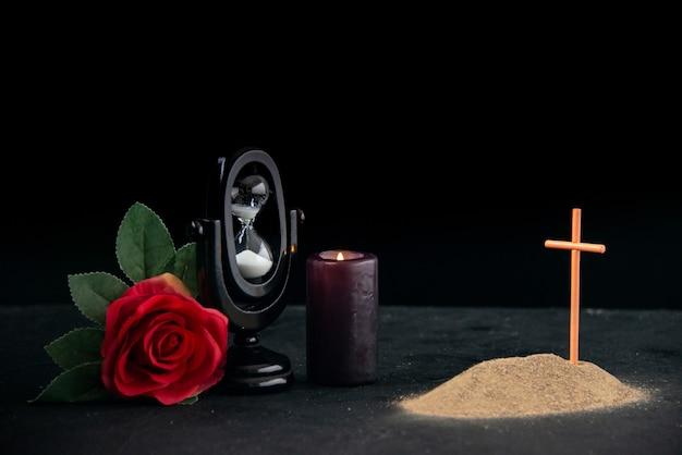 Piccola tomba con fiore rosso e clessidra come ricordo sulla superficie scura