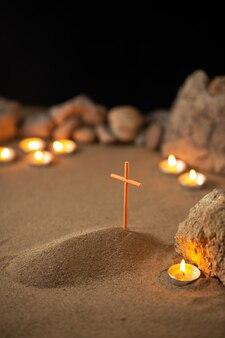 Piccola tomba con pietre e candele accese sulla superficie scura
