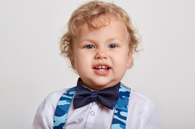 Piccolo bel ragazzo riccio con grande bella in camicia bianca con farfallino si trova in camera e bretelle blu, guarda la telecamera