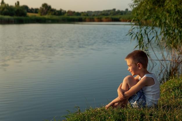 Un ragazzino felice che indossa pantaloncini da bagno seduto sulla riva di uno stagno al tramonto