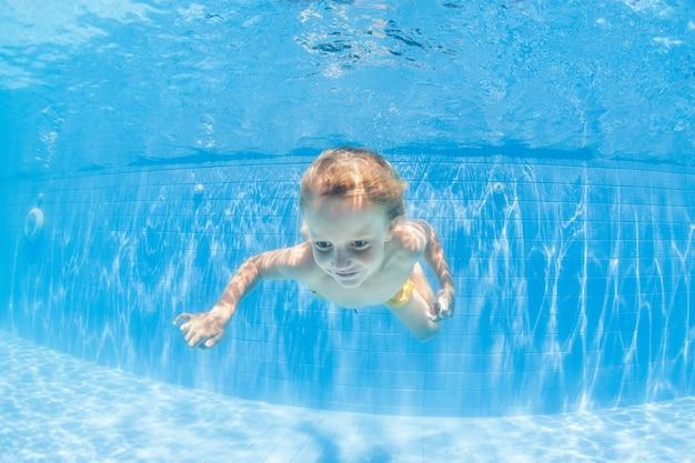 Piccolo bambino felice tuffarsi sott'acqua in piscina
