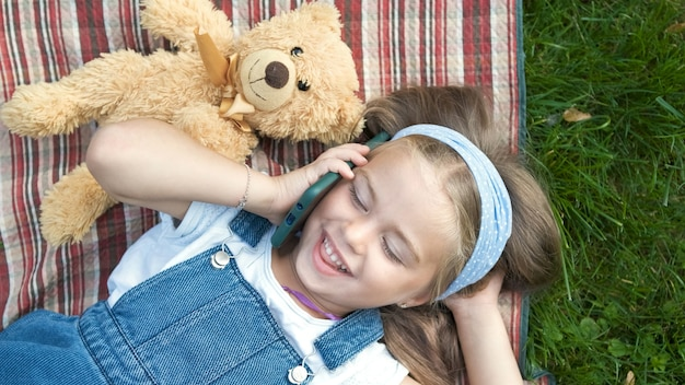 Piccola ragazza felice del bambino che pone su una coperta sul prato verde in estate con il suo orsacchiotto che parla sul telefono cellulare