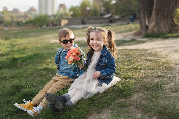 Piccolo ragazzo carino felice e una piccola ragazza carina che si siede sull'erba