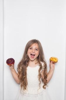 La piccola ragazza prescolare sveglia felice sta mangiando le ciambelle colorate su fondo bianco isolato.