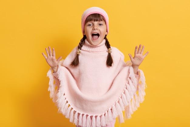 Piccola bambina felice che indossa poncho rosa e berretto che urla allegramente con i palmi sollevati, tiene la bocca ampiamente aperta