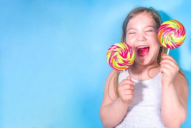 Piccola ragazza felice e divertente con grandi lecca-lecca colorati, vacanze, felicità, concetto di vacanze estive,