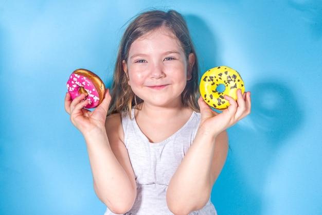 Piccola ragazza felice e divertente con ciambelle rosa e gialle smaltate di zucchero colorato, vacanze, felicità, concetto di vacanze estive,