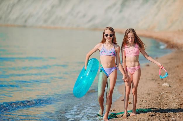 Piccole ragazze divertenti felici si divertono molto in spiaggia a giocare insieme