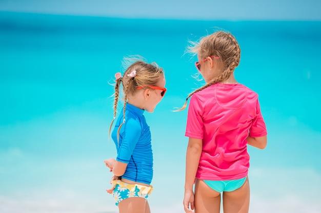 Piccole ragazze divertenti felici si divertono molto in spiaggia tropicale giocando insieme.