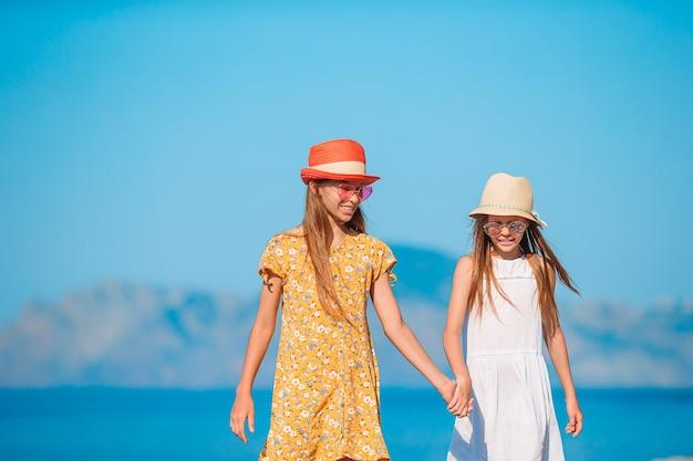 Piccole ragazze divertenti felici si divertono molto in spiaggia tropicale giocando insieme