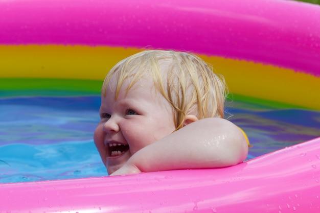 La piccola ragazza felice bagna in uno stagno gonfiabile