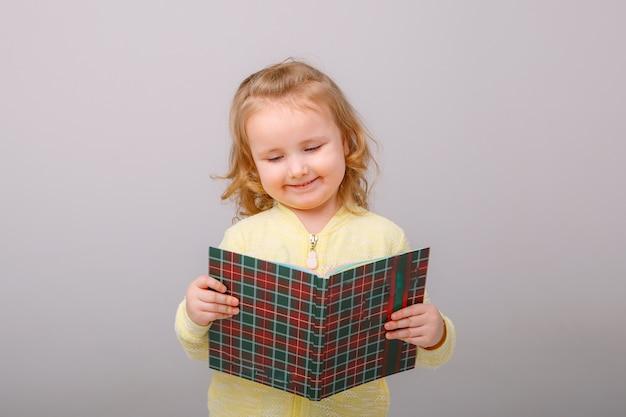 Bambina felice bambino sorpreso con un libro in mano isolato su uno sfondo grigio. concetto di educazione