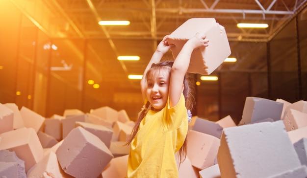 Bambina felice che gioca e si diverte in una piscina a secco con cubetti di paralon in un centro di intrattenimento per bambini
