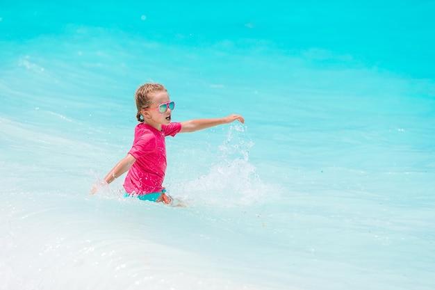 Piccola ragazza felice che spruzza in acqua turquiose chiara