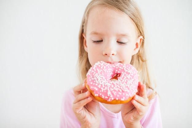 Bambina felice con i capelli biondi, giocando e gustando ciambelle con glassa rosa alla celebrazione di hanukkah