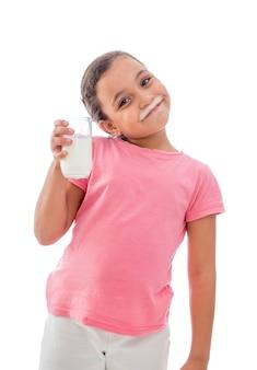 Bambina felice con un bicchiere di latte