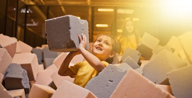 Bambine felici giocano e si divertono in una piscina a secco con cubetti di paralon in un centro di intrattenimento per bambini