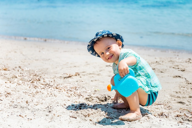 Piccolo bambino felice sta giocando con un annaffiatoio giocattolo con sabbia e acqua sulla spiaggia.