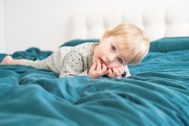Piccolo ragazzo in buona salute del bambino in pigiama verde divertendosi sdraiata a letto a casa.