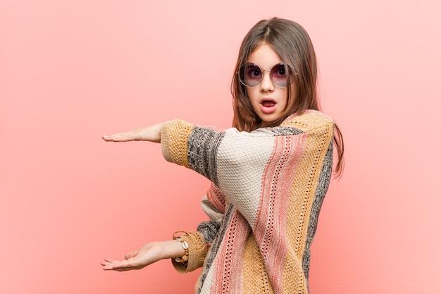 Piccola ragazza hippie scioccata e stupita tenendo una copia spazio tra le mani.