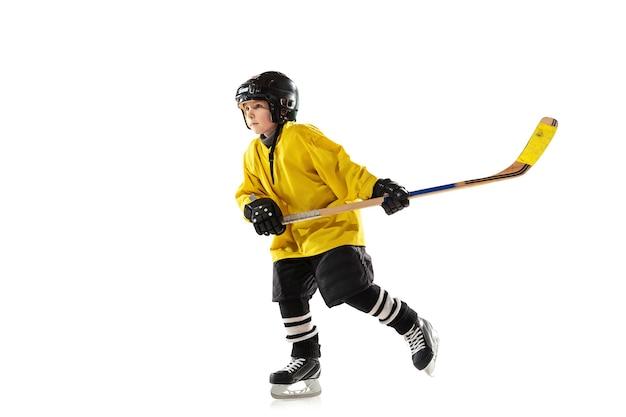 Piccolo giocatore di hockey con il bastone sul campo da ghiaccio e bianco