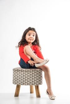 Piccola ragazza indiana che indossa scarpe mentre è seduto su un piccolo sgabello, isolato su sfondo bianco