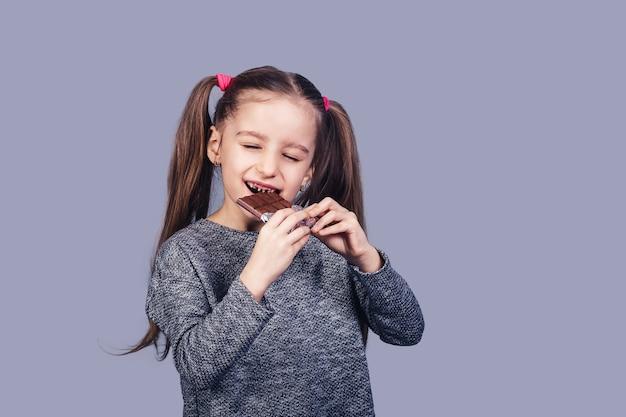La piccola ragazza allegra mangia il cioccolato e mostra i suoi denti affetti da carie. isolato su superficie grigia