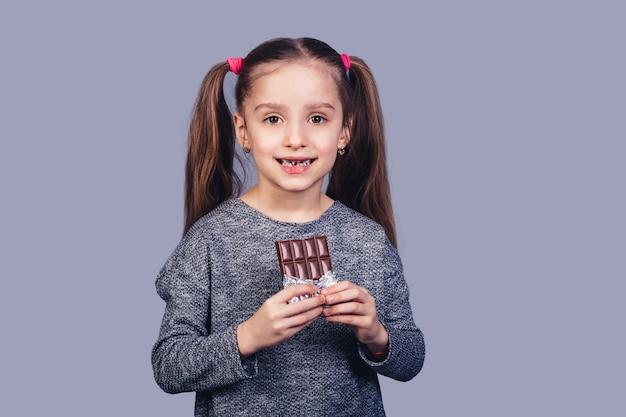La piccola ragazza allegra tiene il cioccolato nelle sue mani e mostra i suoi denti affetti da carie. isolato su superficie grigia