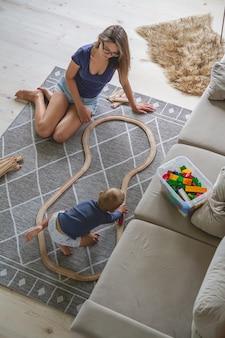 Ragazzino e sua madre che giocano con la ferrovia Foto Premium