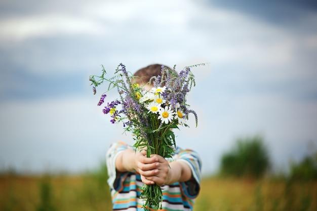 Ragazzino che tiene in mano un mazzo di fiori di campo con sfondo azzurro del cielo