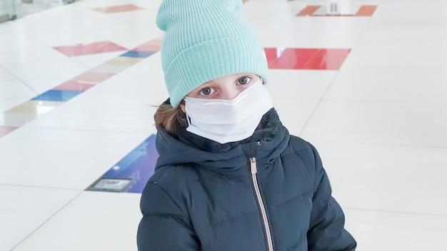 Piccolo bambino il bambino indossa un cappotto e un cappello. maschera per la protezione dell'epidemia di coronavirus. nuovo coronavirus 2019-ncov dalla cina. maschera igienica facciale per sicurezza, virus e influenza