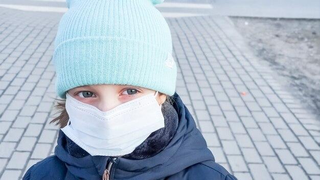Ragazzino, il bambino indossa un cappotto e un cappello, per strada. maschera per la protezione dell'epidemia di coronavirus. coronavirus 2019-ncov dalla cina. maschera igienica facciale per sicurezza, virus e influenza