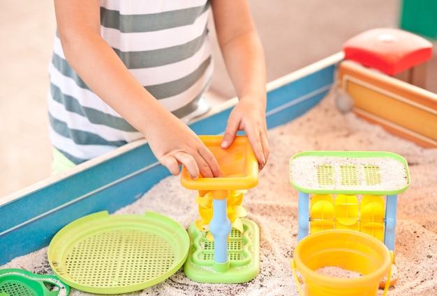 Bambina che gioca nel parco giochi all'aperto con sabbia e giocattoli